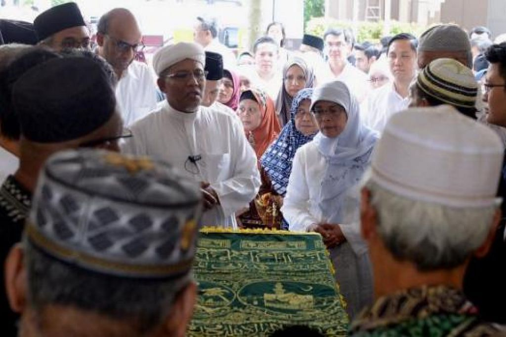 DETIK SAYU: Cik Halimah (bertudung putih), dikelilingi tetamu, termasuk Timbalan Perdana Menteri, Encik Tharman Shanmugaratnam, sebelum jenazah ibunya dibawa dari rumah beliau ke Masjid Darul Makmur.