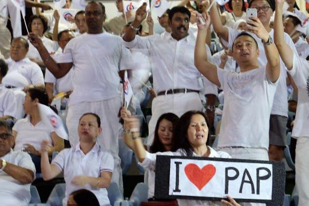 BAGAI PESTA: Penyokong PAP berhimpun di Stadium Bedok bagi memberi sokongan kepada calon-calon yang bertanding. - Foto-foto THE STRAITS TIMES