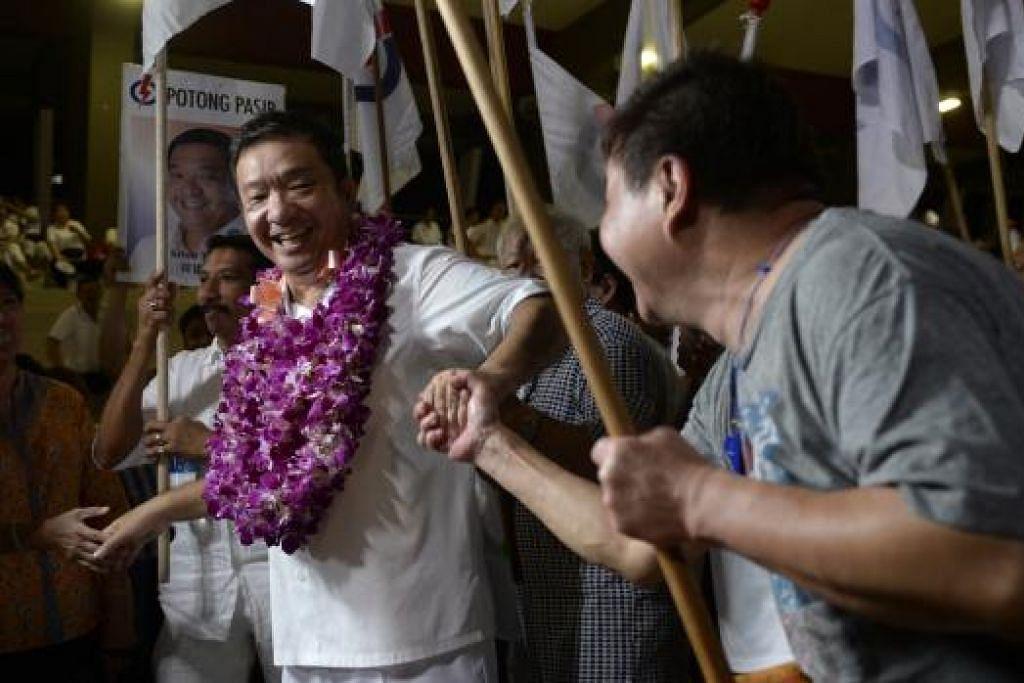 RAIH UNDI LEBIH BESAR: Encik Sitoh Yih Pin dikerumuni penyokongnya mempertahankan kerusinya di SMC Potong Pasir dengan meraih undi 66.41 peratus. - Foto-foto THE STRAITS TIMES