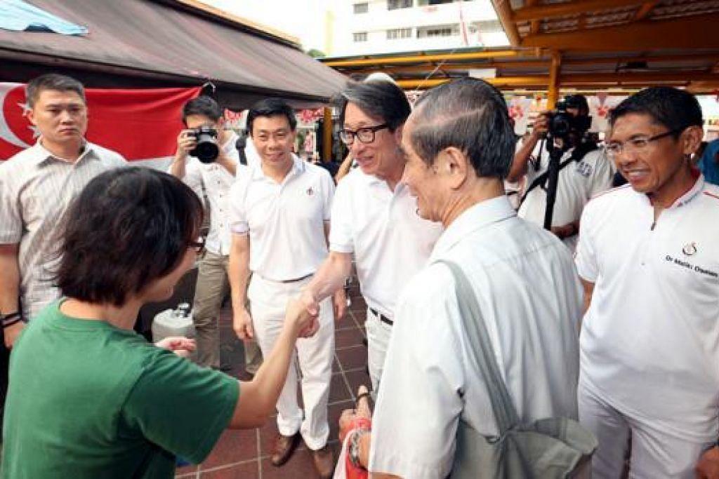 PASUKAN GRC EAST COAST: Encik Lee Yi Shyan (tiga dari kiri), Encik Lim Swee Say (berjabat tangan) dan Dr Maliki Osman (kanan) menemui penduduk pagi semalam bagi mengucapkan terima kasih atas sokongan mereka. - Foto THE STRAITS TIMES