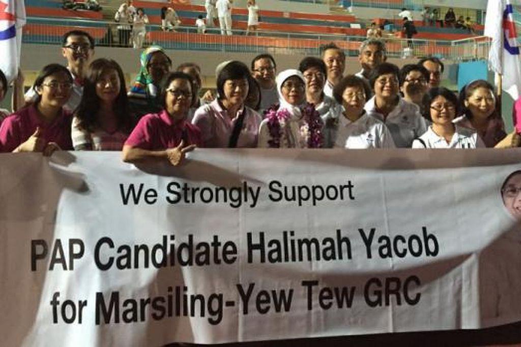 REBUT PELUANG: Para penyokong dan aktivis merebut peluang bergambar bersama Cik Halimah Yacob (tengah) setelah PAP diumumkan menang di GRC Marsiling-Tew Tee.– Foto ERVINA MOHD JAMIL