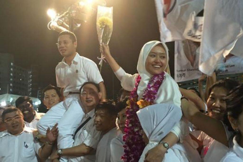 MERIAH: Encik Desmond Lee (kiri) dan Cik Rahayu Mahzam dijulang penyokong mereka yang tidak berhenti-henti memberi sorakan kuat atas kemenangan pasukan PAP GRC Jurong. – Foto ERVINA MOHD JAMIL