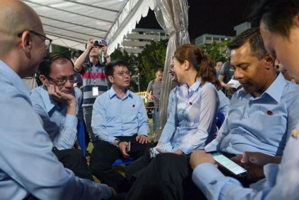 MENANTI KEPUTUSAN: Calon-calon Parti Pekerja (WP) duduk bersembang di Stadium Hougang sementara menunggu keputusan pilihan raya diumumkan. – Foto KUA CHEE SIONG