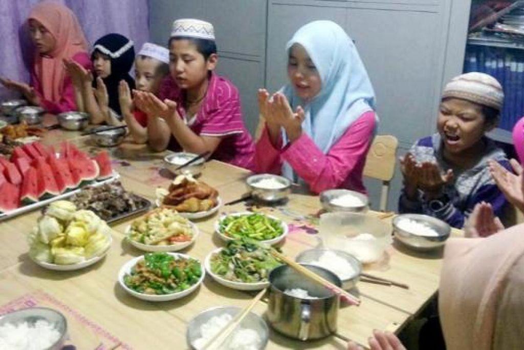 MENGHIMPUN DOA: Kanak-kanak Muslim China memanjatkan kesyukuran mendapat rezeki makanan, termasuk daging korban sempena Hari Raya Aidiladha. - Foto ihsan ADAM LEE
