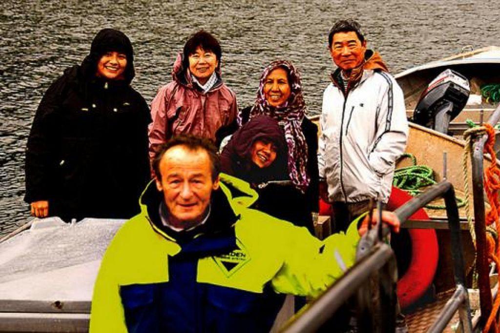 KENANGAN: Encik Michael Walford (depan) tersenyum membawa penulis (tiada dalam gambar) dan isteri (kedua dari kanan) serta teman-teman dari Jepun ke seberang ke Pulau Scalpay dengan motobotnya. - Foto MOKSIM SALEH