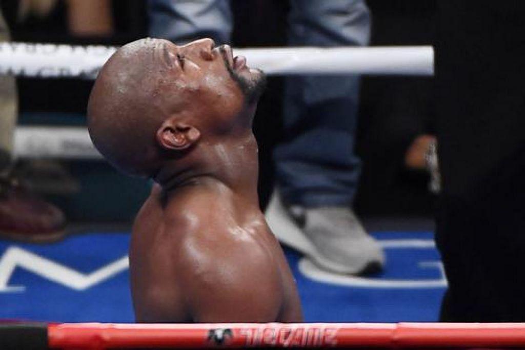 TERIMA KASIH: Mayweather melutut dan mendungak selepas keputusan kemenangannya diumumkan. - Foto AFP
