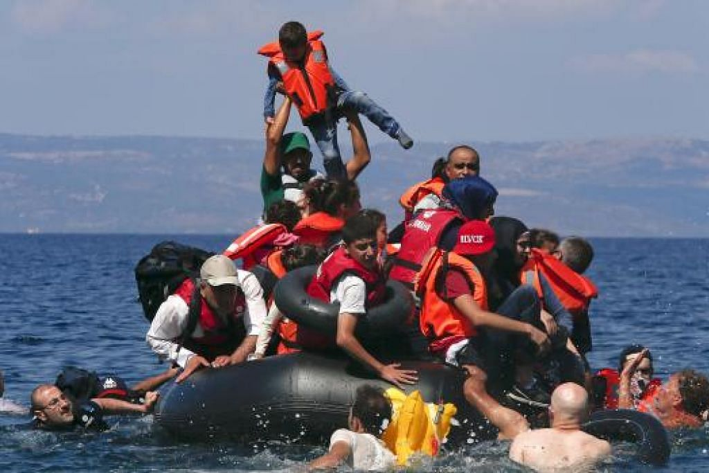Seorang kanak-kanak diangkat sedang pelarian Syria dan Afghanistan berkumpul di dalam dan sekitar sebuah dingi yang kempis sekitar 100 meter dari sebuah pulau Greece, Lesbos, pada Ahad (13 September). Pada hari sama, sebuah bot pelarian karam, mengakibatkan 34 orang, termasuk 15 bayi dan kanak-kanak terkorban. Gambar REUTERS