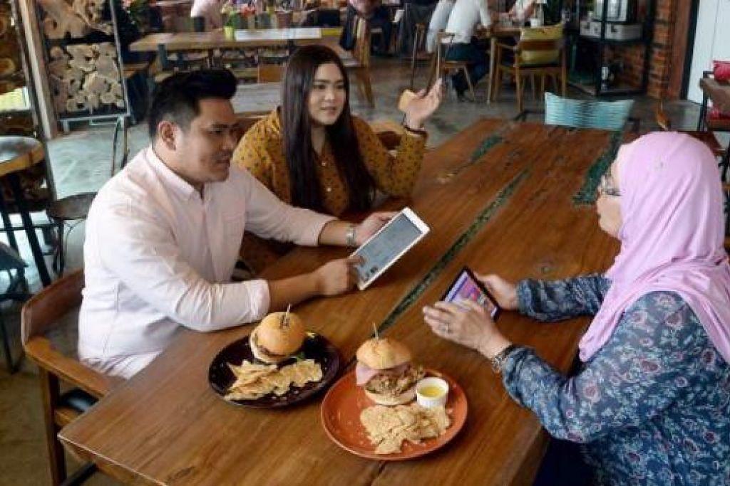 PERNIAGAAN KELUARGA: Encik Ahmad Firdaus dan Cik Aina beruntung kerana boleh mendapat bantuan ibu mereka, Cik Jalilah Ahmat (kanan), dalam operasi harian kafe mereka. - Foto TAUFIK A. KADER