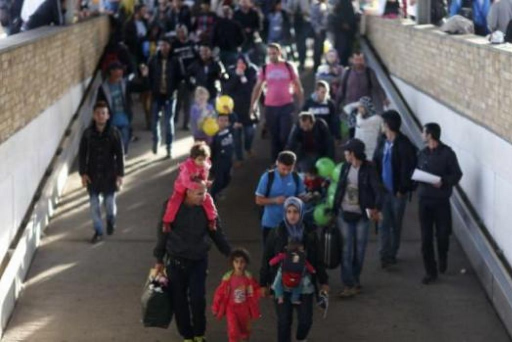 TERUS TIBA: Pendatang tiba dengan kereta api di stesen kereta api Schoenefeld, di selatan Berlin, Jerman, kelmarin. - Foto REUTERS