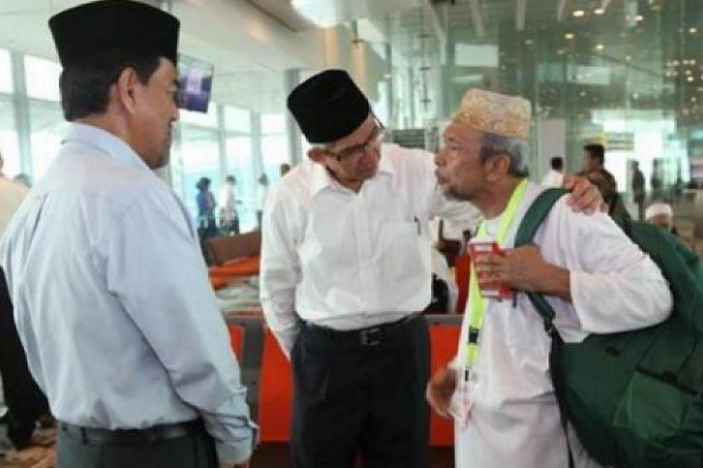 SELAMAT BERIBADAH: Dr Yaacob (tengah) berbual dengan salah seorang jemaah haji tahun ini yang berangkat ke Jeddah petang semalam sambil disaksikan Ketua Eksekutif Muis, Haji Abdul Razak Maricar. - Foto MUIS