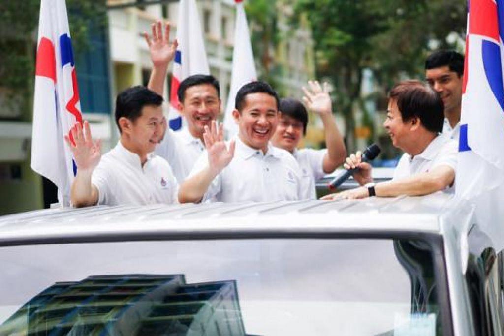 TERIMA KASIH!: Encik Amrin Amin (tengah) bersama pasukan PAP GRC Sembawang melahirkan penghargaan kepada pengundi semasa perarakan kemenangan semalam. - Foto ihsan FANDY RAZAK