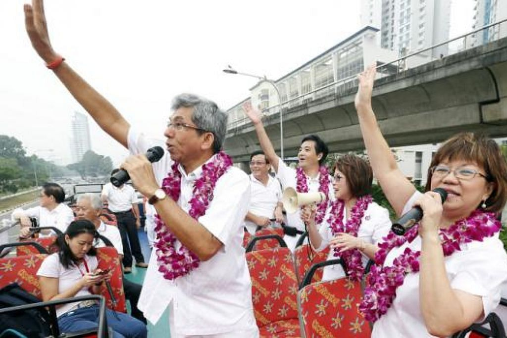 RAI KEMENANGAN: (Dari kiri memakai kalungan bunga) Dr Yaacob bersama anggota pasukannya Encik Heng Chee How, Dr Lily Neo dan Cik Denise Phua di atas bas mengelilingi GRC Jalan Besar. - Foto THE STRAITS TIMES