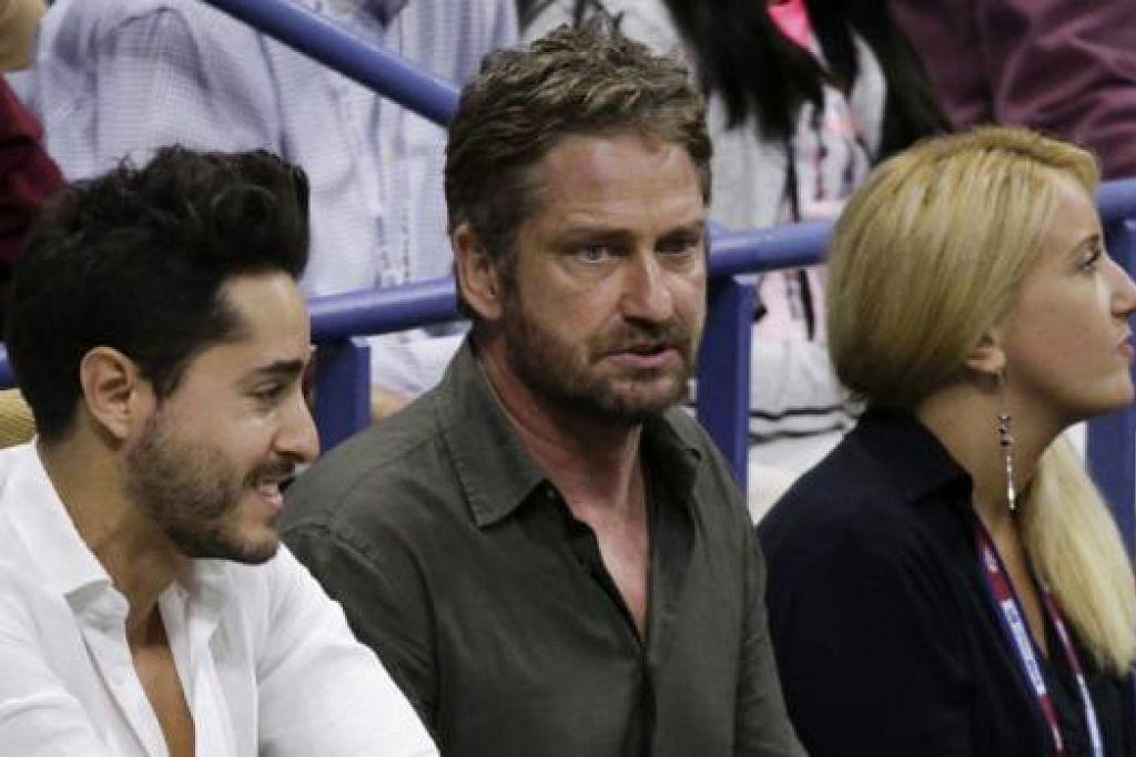 TETAMU GLAMOR: Bintang filem asal Scotland, Gerard Butler (tengah), di kalangan penonton di final antara Djokovic dengan Federer. - Foto REUTERS