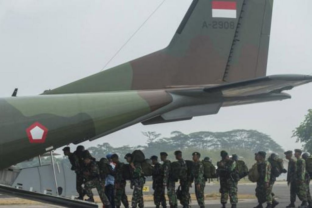 BERANGKAT KE 'MEDAN JUANG': Askar Indonesia sedang menaiki sebuah pesawat tentera negara itu di Pangkalan Tentera Udara Halim untuk menyertai rakan mereka yang sedang memerangi kebakaran hutan di wilayah Riau. - Foto REUTERS