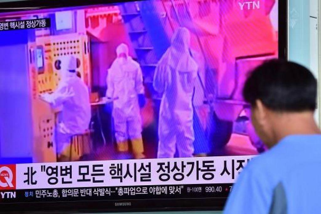 Seorang lelaki menonton laporan berita di sebuah stesen kereta api di Seoul pada 15  September mengenai pengumuman Korea Utara bahawa reactor nuklearnya di Yongbyon  telah menyambung semula operasi biasa sepenuhnya. Gambar AFP