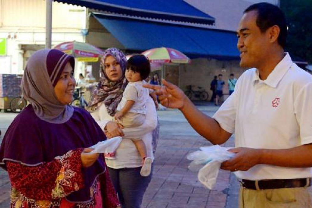 KHIDMAT KEPADA KAKI BUKIT: Encik Shamsul (kanan) mengedarkan pelitup muka N95 kepada penduduk di luar Sheng Siong di Bedok North Street 3. - foto TUKIMAN WARJI