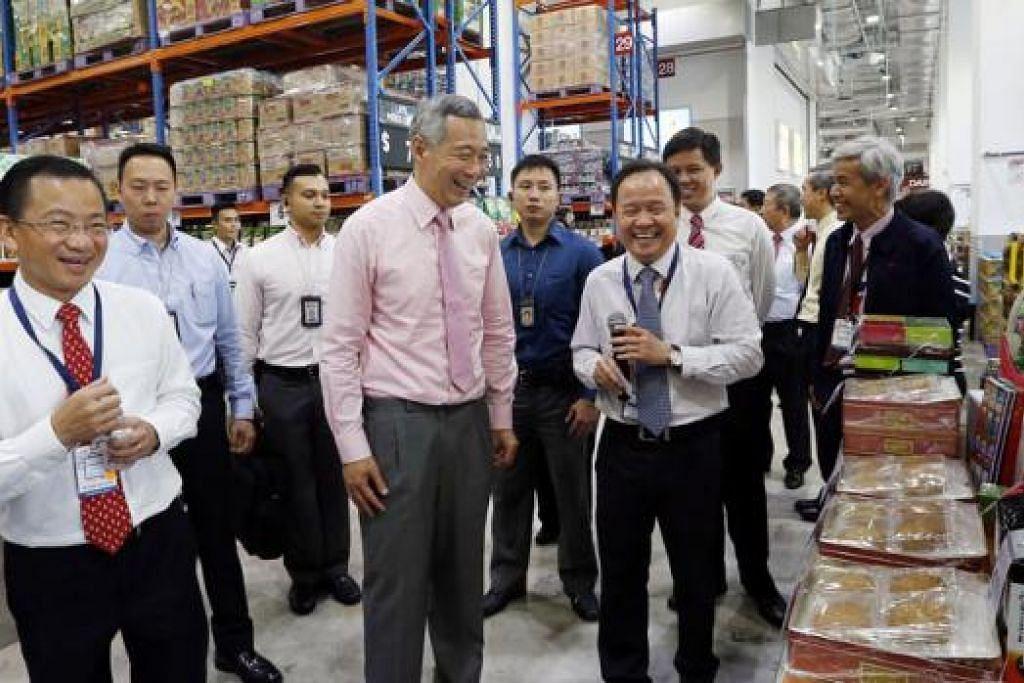 HAB FAIRPRICE: Encik Lee sambil diiringi (paling kiri) Encik Seah Kian Peng, Ketua Pegawai Eksekutif NTUC Fairprice Co-operative, meninjau gudang runcit yang terletak di dalam Hab FairPrice. - Foto THE STRAITS TIMES