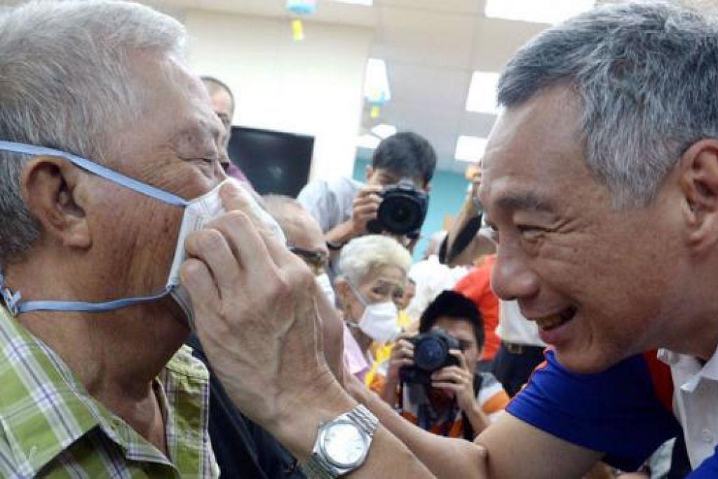 TUNJUK CARA BETUL: Encik Lee menunjukkan cara betul memakai pelitup kepada seorang warga tua di COMNET@Pusat Aktiviti Warga Emas Teck Ghee di Ang Mo Kio semalam. - Foto TAUFIK A. KADER