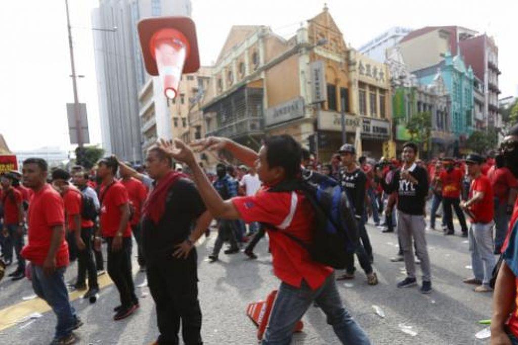 Seorang peserta perhimpunan 'Baju merah' melempar kon trafik ke arah polis rusuhan. Gambar REUTERS