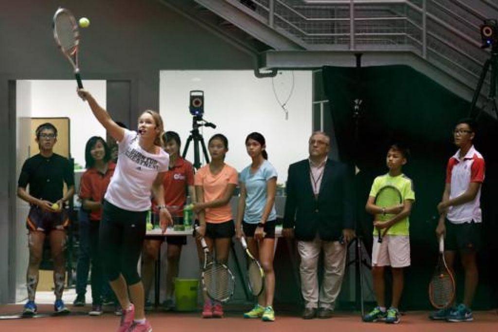 TUNJUK BAKAT: Wozniacki menunjukkan cara betul membuat servis kepada pemain-pemain muda yang mengikuti klinik tenis kendalian beliau di Institut Sukan Singapura semalam. - Foto THE STRAITS TIMES