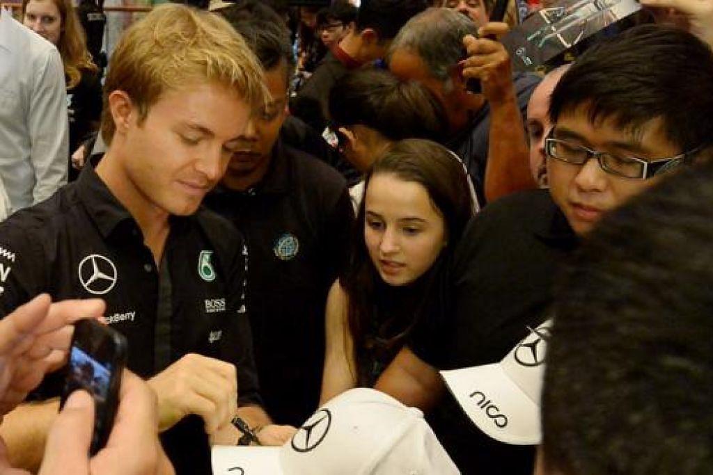 LAYAN PEMINAT: Nico Rosberg (kiri) sedang menurunkan autograf beliau pada topi salah seorang peminatnya. - Foto TUKIMAN WARJI