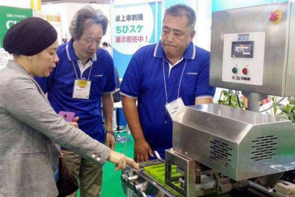 TINJAU TEKNOLOGI BARU: Cik Samsiah meninjau mesin yakitori yang boleh disesuaikan bagi menghasilkan sate di Singapura. - Foto SPC