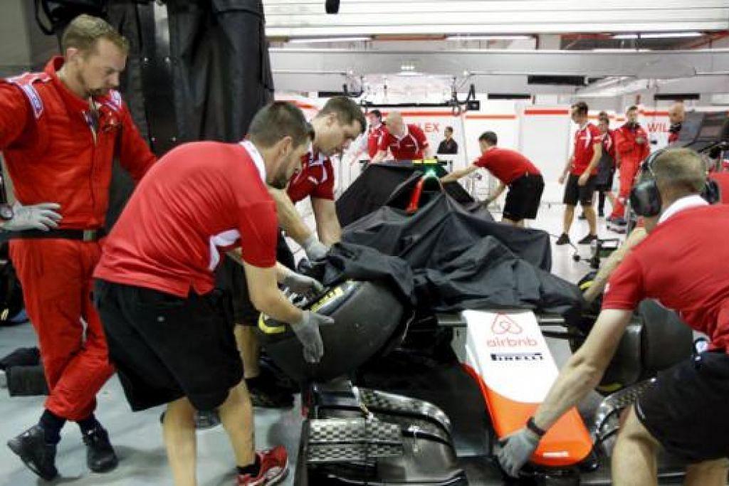 ROSAK: Kru pasukan Marussia Manor sedang menolak kereta Alexander Rossi yang rosak dan kemik sedikit selepas pemandu rookie Amerika Syarikat itu merempuh tembok. - Foto REUTERS
