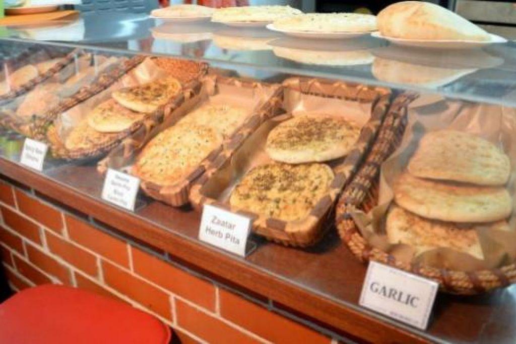 PANAS DAN SEGAR: Biarpun kedainya agak kecil, dalam sehari Pita Bakery milik Encik Yuri Ustaev ini mampu menghasilkan ribuan keping roti (gambar). Untuk mengekalkan kesegarannya, roti pita di kedai ini tidak akan melebihi tiga jam apabila dijual kepada pelanggan. - Foto-foto JOHARI RAHMAT