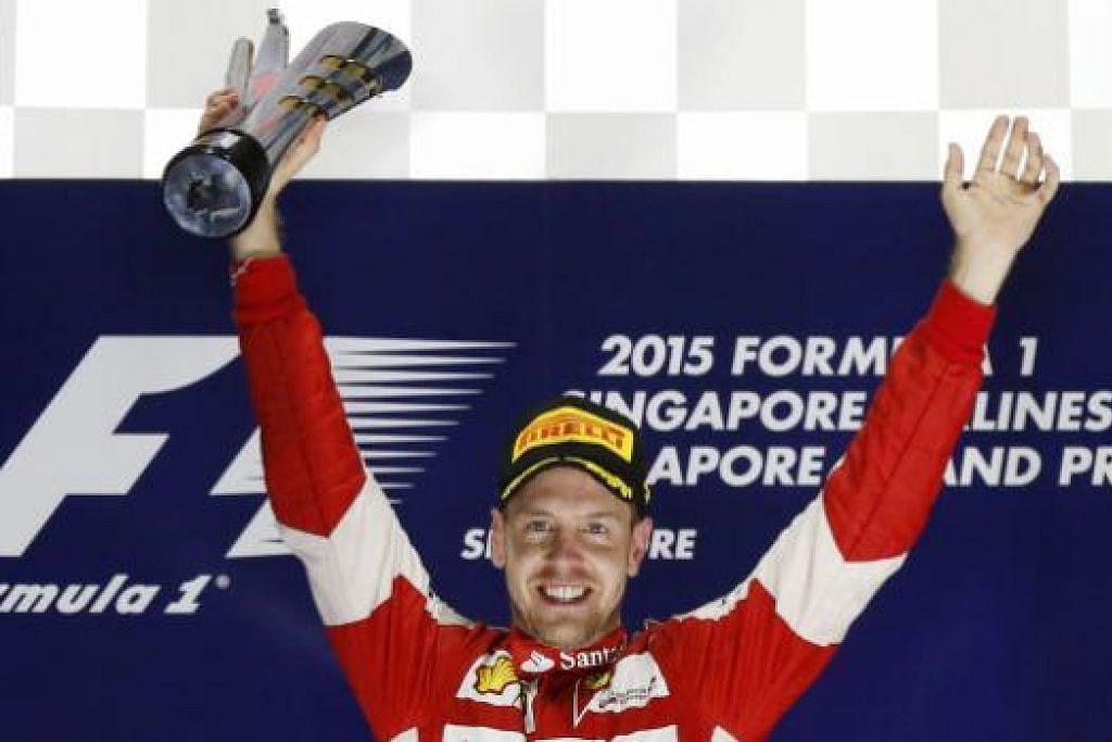 RAJA DI MARINA BAY: Pemandu Jerman, Sebastian Vettel, dengan piala kemenangannya - kali keempat beliau menjuarai perlumbaan di Grand Prix Singapura.
