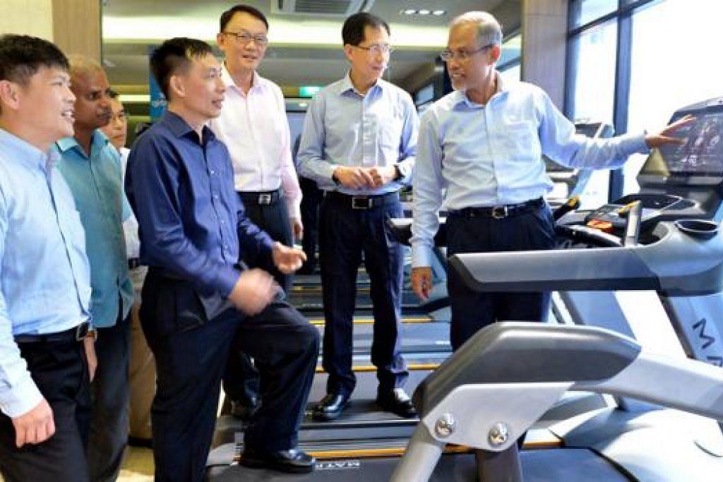 KEMUDAHAN BARU: Encik Masagos (kanan) melihat peralatan di gim di Kelab HomeTeamNS Sembawang yang dibuka semula setelah menjalani kerja ubah suai selama enam bulan bernilai $4 juta. - Foto M.O. SALLEH