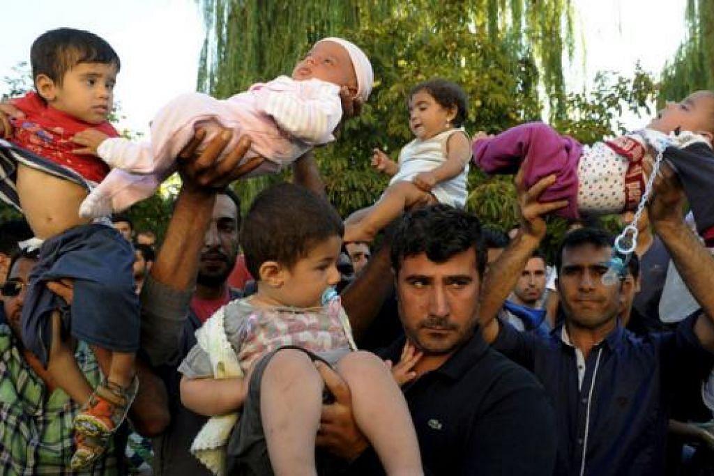 MINTA DIBENARKAN MASUK: Pelarian semalam mengangkat anak mereka sedang mereka membantah supaya dapat dibenarkan masuk ke Greece, dekat bandar pelabuhan Edirne, Turkey. - Foto REUTERS