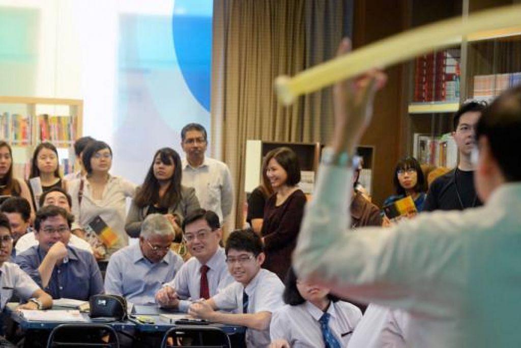 KELAS DEMONSTRASI FIZIK: Menteri Pendidikan, Encik Heng Swee Keat (duduk, dua dari kanan), menyertai kelas fizik bersama pelajar semasa pelancaran Pusat bagi Kecemerlangan Pengajaran & Pembelajaran. - Foto THE STRAITS TIMES