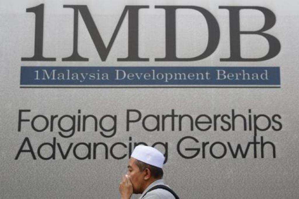 HADAPI BEBAN HUTANG DAN DAKWAAN RASUAH: Lelaki ini menutup mulutnya sambil berjalan lalu di hadapan papan tanda 1 Malaysia Development Berhad (1MDB), yang kini dibelenggui bebanan hutang dan dakwaan rasuah. - Foto-foto REUTERS