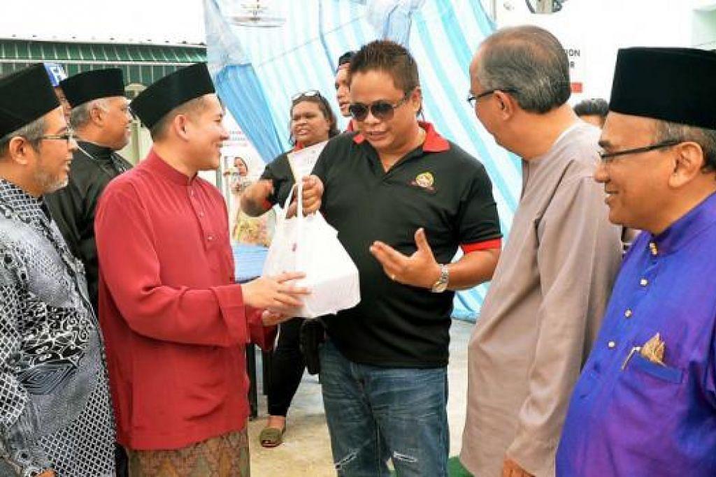 SEMANGAT MENYUMBANG: Encik Amrin (kedua dari kiri) sempat beramah mesra dengan Encik Hazzan (tengah), yang mengetuai kumpulan penunggang motosikal, mengagihkan daging korban. Mereka diperhatikan (dari kanan) oleh Encik Mohd Noor, anggota ekso Jamiyah; dan Dr Isa Hassan, Naib Presiden III Jamiyah; serta Encik Mohd Yunos Mohd Shariff, Naib Presiden II Jamiyah (kiri). - Foto KHALID BABA
