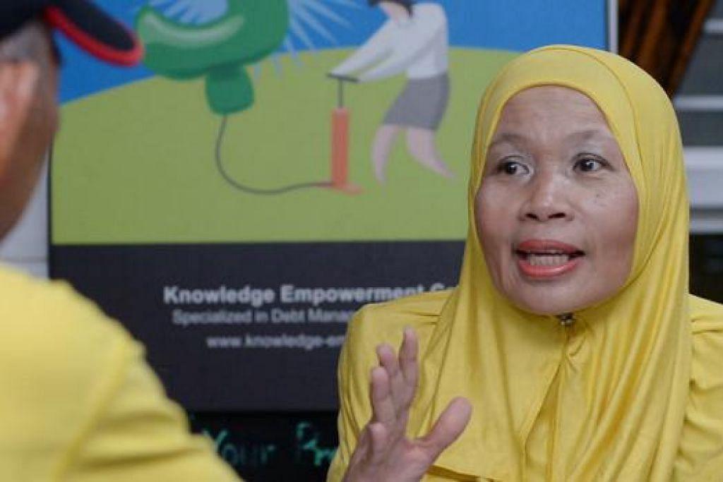 NASIHAT HURAI MASALAH: Dr Kadariah sedang berunding dengan pelanggannya mengenai pilihan yang boelh diambil bagi menghuraikan masalah hutangnya. - Foto TUKIMAN WARJI