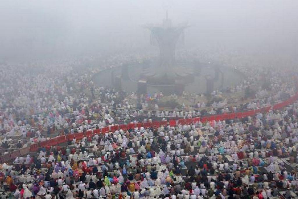 Jemaah menunaikan solat Hari Raya Haji dalam keadaan diselubungi jerebu di Masjid  Agung di Palembang, Sumatera, pada Khamis (24 Sep).  REUTERS