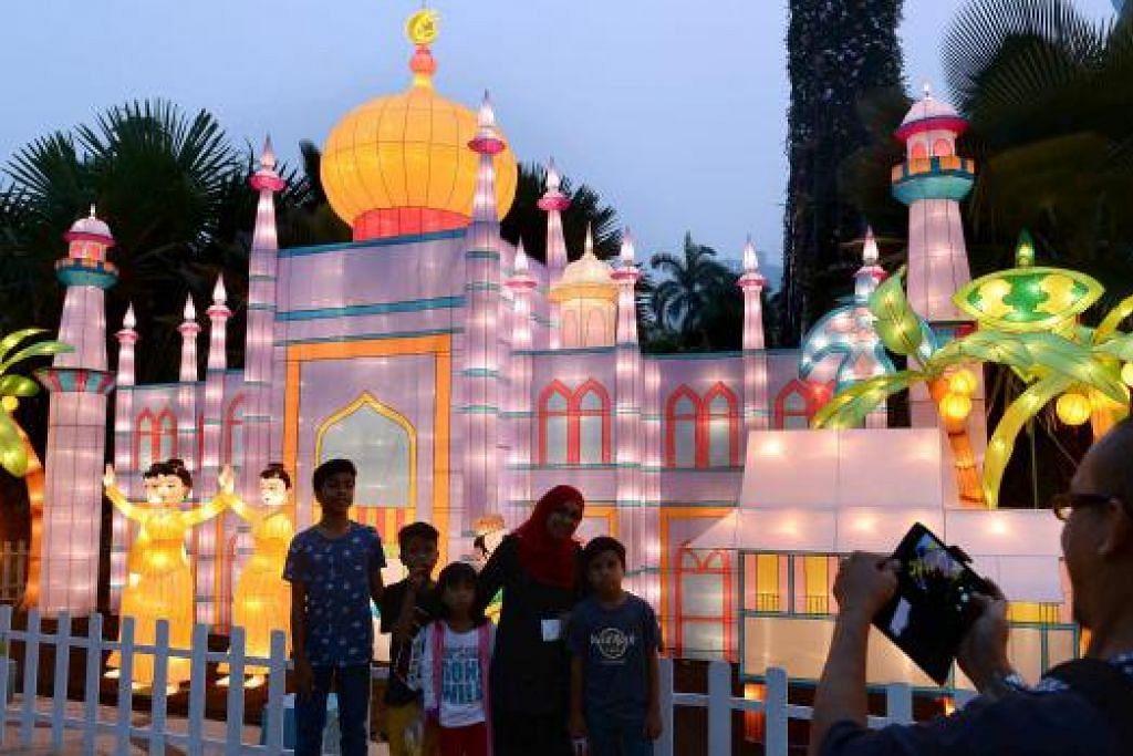 WARNA WARNI: Pelancong dari Malaysia Encik Azlie Ramli merakamkan foto keluarganya di hadapan gubahan Masjid Sultan sempena Pesta Musim Luruh di Taman di Persisiran. - Foto TAUFIK A. KADER