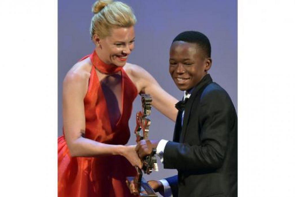 TERIMA ANUGERAH: Abraham Attah, yang tidak mempunyai pengalaman dalam bidang lakonan, menerima Anugerah Aktor Muda Terbaik Marcello Mastroianni di Festival Filem Venice 2015 di Italy daripada aktres dan pengarah filem Amerika Syarikat, Elizabeth Banks. - Foto AFP