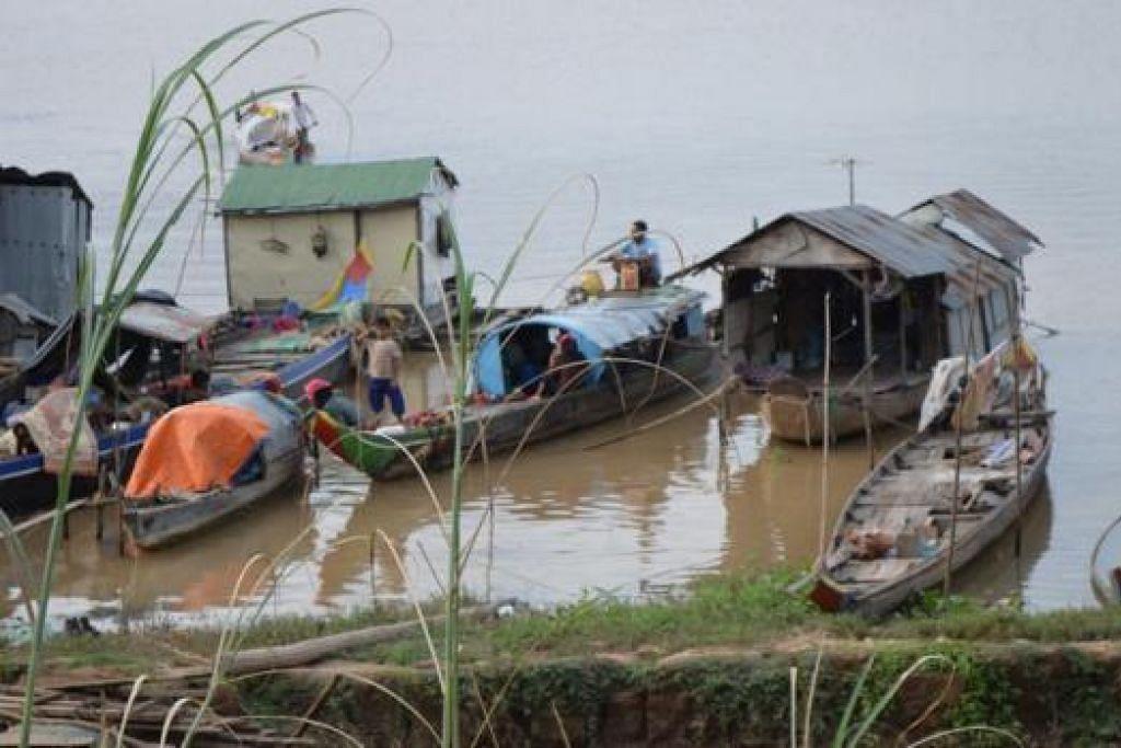 KEDIAMAN MENARIK: Penulis sekeluarga menyaksikan penduduk menetap dalam rumah sampan di Kampung Svay Rolum, Kandal, Kemboja. - Foto-foto MOHAMAD FAIRUS A. RAHMAN