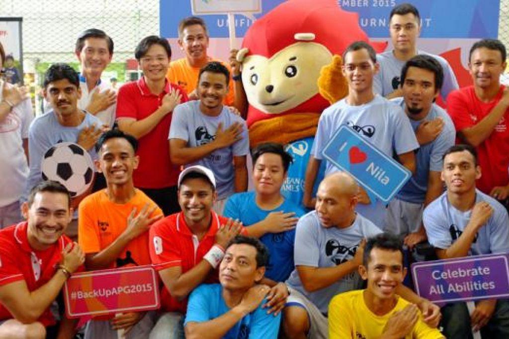 SEMARAKKAN SEMANGAT KESUKANAN: Encik Lawrence Wong (berdiri, empat dari kiri) bergambar kenangan bersama pemain bola sepak pasukan Cerebral Palsy Singapura dan bekas pemain Singapura termasuk Fandi Ahmad (berdiri di kanan). - foto HAKIM YUSOF