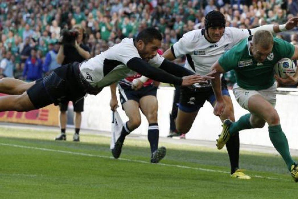 GAGAL DIADANG: Pemain sayap Ireland, Keith Earls (jersi hijau), memecut bagi mencatatkan satu lagi 'try' pasukannya sekalipun cuba dipintas dua pemain Romania. - Foto AFP