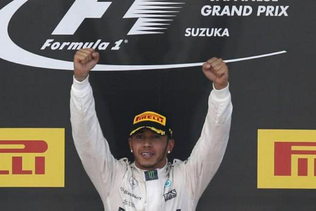 AKSI JUARA: Hamilton mengangkat kededua tangannya selepas muncul sebagai juara dalam Grand Prix Jepun kelmarin. - Foto REUTERS