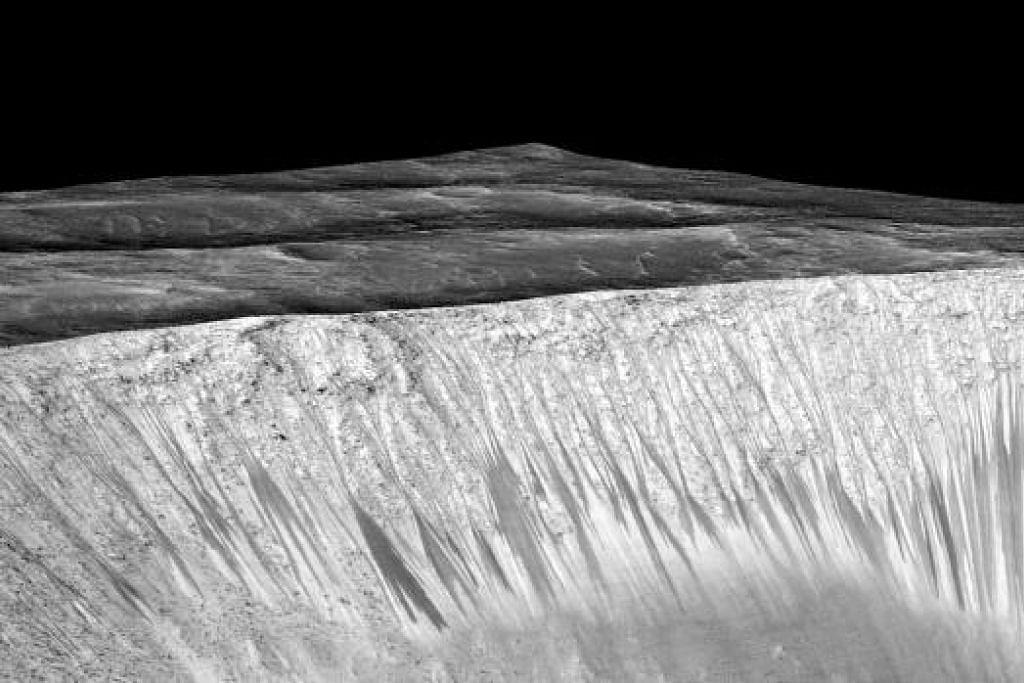 Jalur-jalur gelap pada tembok kawah Garni di Marikh kelihatan dalam imej yang dihasilkan Nasa, Jet Propulsion Laboratory (JPL) dan Universiti Arizona ini. Saintis telah menemui bukti pertama bahawa air masin mungkin mengalir pada permukaan Marikh semasa musim panas di planet itu. Gambar REUTERS
