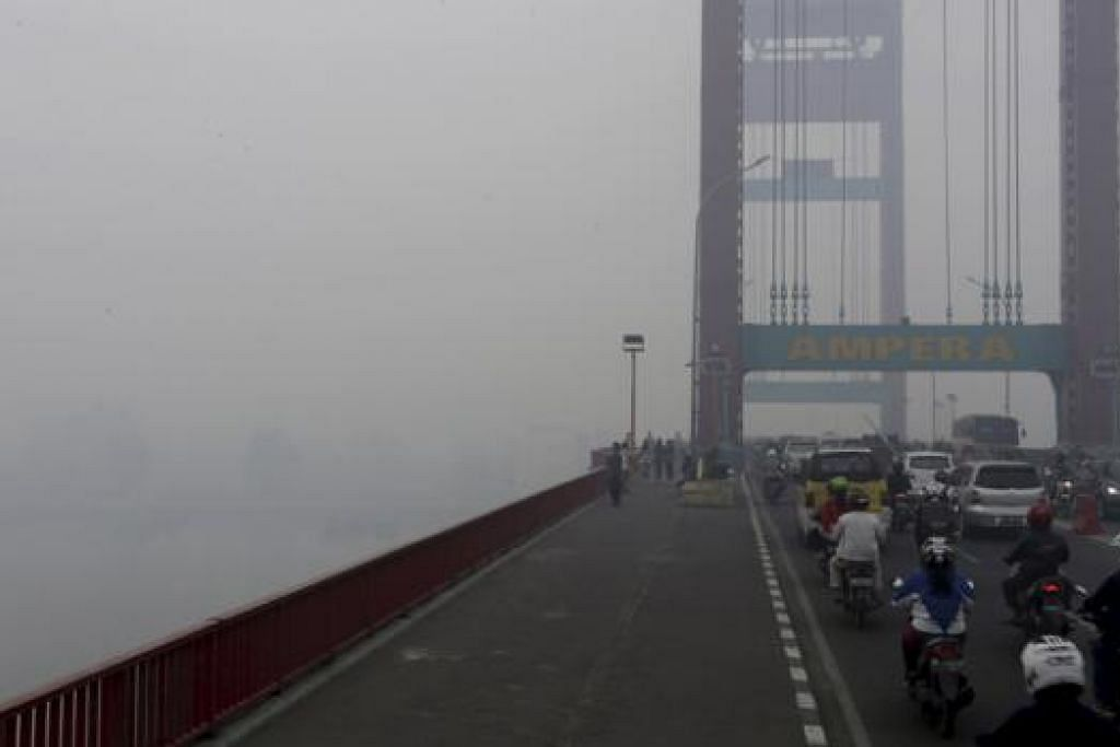 BUKAN DILITUPI KABUS: Jambatan Ampera, yang digunakan kenderaan dan pejalan kaki untuk menyeberangi Sungai Musi di Palembang, di wilayah Selatan Sumatera, Indonesia, diselubungi jerebu sejak beberapa hari lalu. - Foto REUTERS