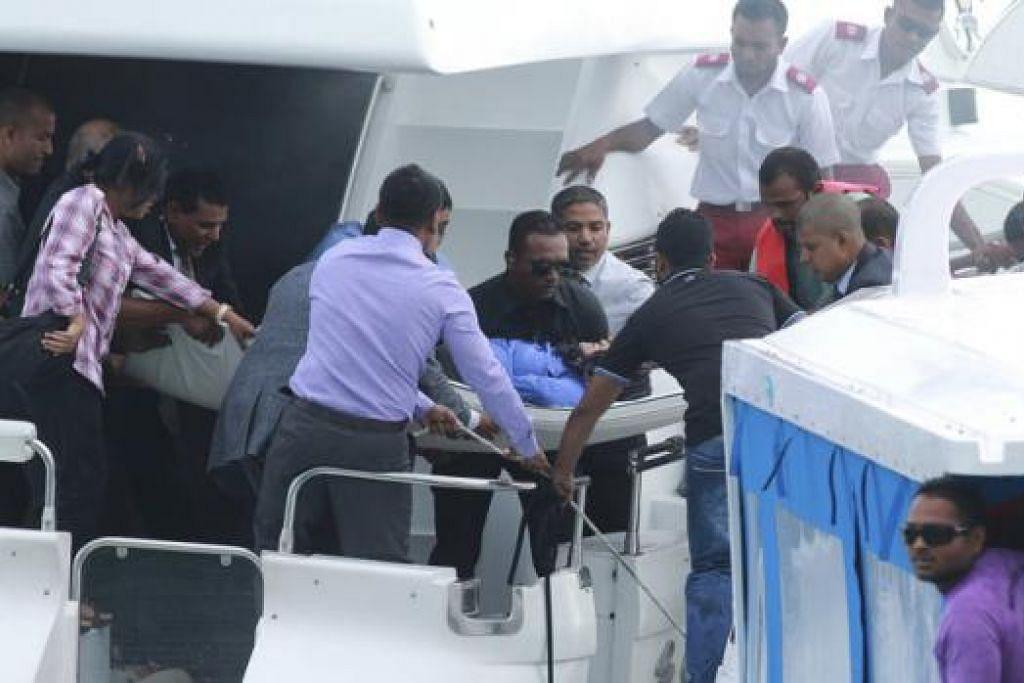 CEDERA: Pegawai mengusung salah seorang wanita yang cedera dari bot laju yang membawa Presiden Maldives, Encik Abdulla Yameen, yang mengalami letupan. Walaupun beliau selamat, isterinya dan dua yang lain cedera. - Foto REUTERS