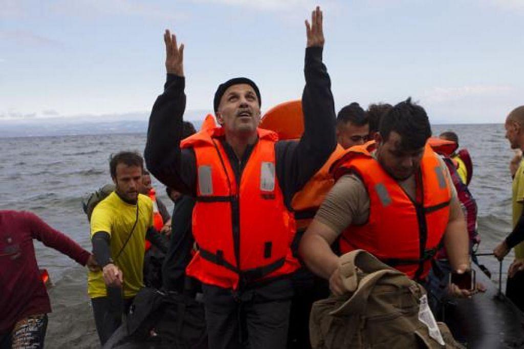 SYUKUR: Seorang pelarian Syria berdoa sebaik saja tiba di Pulau Lesbos di Greece kelmarin selepas menyeberang Laut Aegean dari pantai Turkey. - Foto REUTERS
