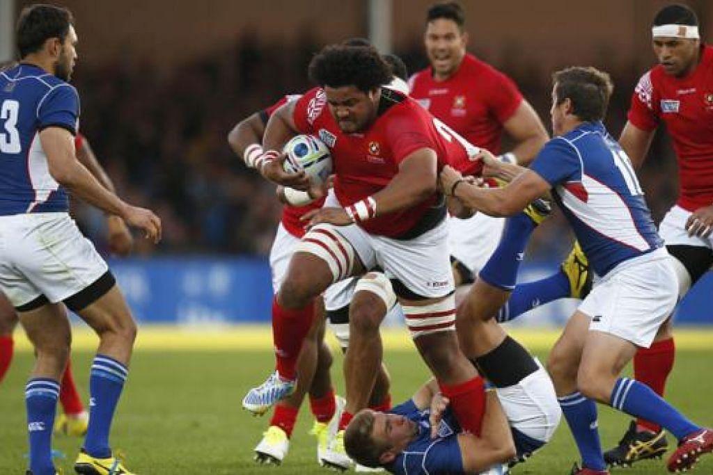 TEMPUR: Pasukan Tonga (jersi merah) sedang beraksi menentang pasukan Namibia (jersi biru) di Piala Dunia Ragbi kelmarin. - Foto REUTERS