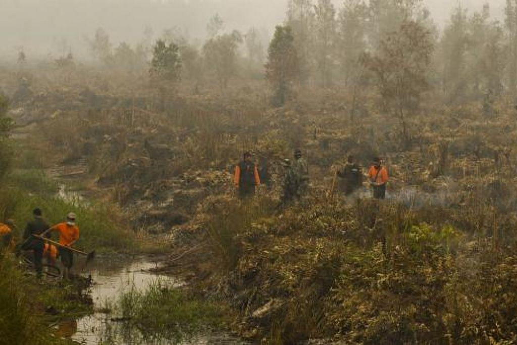 Gambar pada 24 September ini menunjukkan askar dan anggota bomba mendapatkan air dari sebuah terusan bagi memadamkan kebakaran di tanah gambut hutan di Jabiren Raya di Kalimantan Tengah. President Joko Widodo telah mengarahkan lebih banyak terusan dan takungan air dibina dalam usaha mengawal kebakaran hutan. Gambar AFP