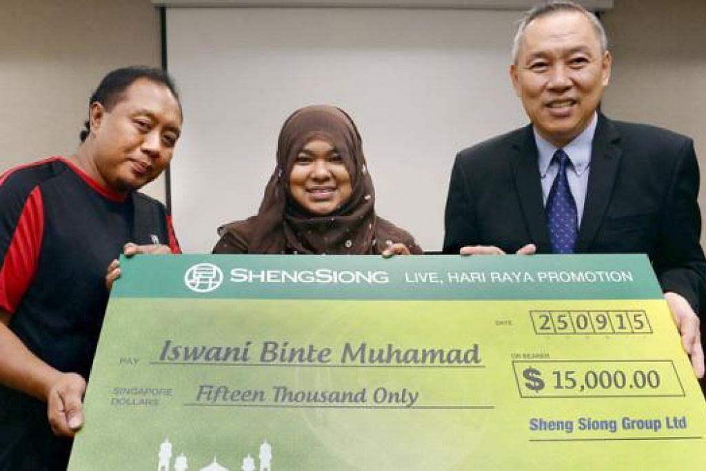 TIDAK DISANGKA: Encik Lim Hock Chee (kanan) menyerahkan cek bernilai $15,000 kepada Cik Iswani Muhamad dan Encik Ya'acob Hassan. - Foto TAUFIK A. KADER