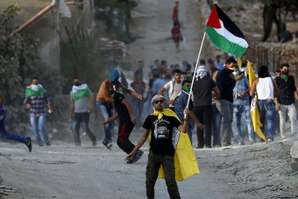 SALING TEMPUR: Sambil mengibar bendera wilayahnya, rakyat Palestin membaling batu ke arah tentera Israel di pekarangan Masjid Al-Aqsa kelmarin. - Foto AFP